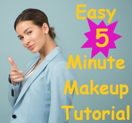 Girl standing sideways looking directly at you in blue business jacket with right arm across body holding hand up with curled middle, ring, and pinky finger. Pointer finger is pointing at you and thumb is up insinuating to the viewer that you got this. Easy 5 Minute Makeup tutorial
